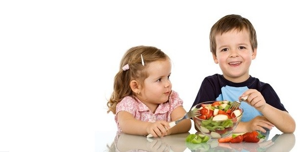 Happy healthy kids eating fruit salad - isolated